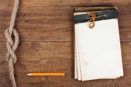 Antique notebook e matita su legno con sfondo corda nodo