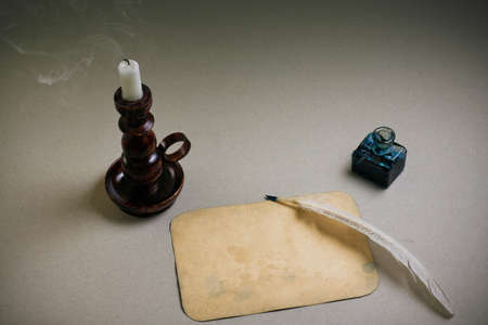 Candle in vintage candlestick, quill and  inkwell, old paper blank Stock Photo - 13679066