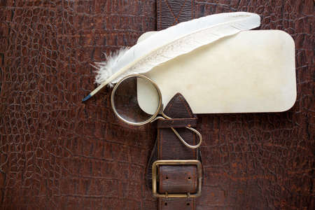 Vintage crocodile leather textured background with magnifying glass, quill and paper frame photo