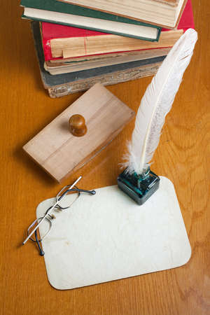 Grunge paper, quill and inkwell, old books, spectacles on wooden table photo