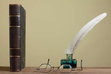 Antikes Buch, Brille, Feder und Tintenfass auf Holztisch Lizenzfreie Bilder
