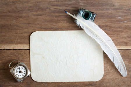 inkwell: Quill pen and inkwell, old grunge paper, vintage clock on wooden table