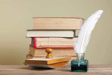Quill and inkwell,  blotter, old books on wood photo