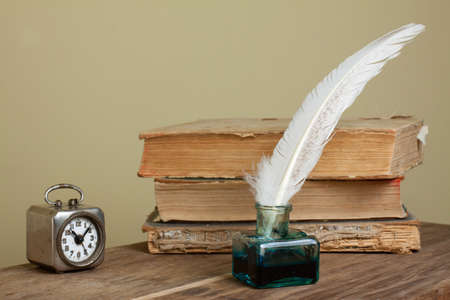 Quill and inkwell, old books, vintage clock on grunge wooden table photo