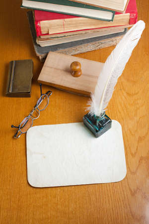 Grunge paper, quill and inkwell, old books, spectacles, blotter on wooden table photo