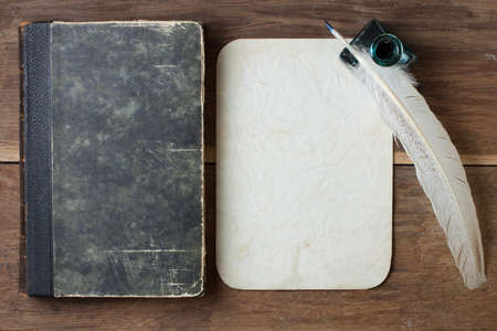 Book cover, quill and inkwell, old grunge paper on wood background photo