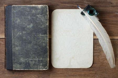 Buchcover, Federkiel und Tintenfass, alte Grunge Hintergrund Papier auf Holz Lizenzfreie Bilder