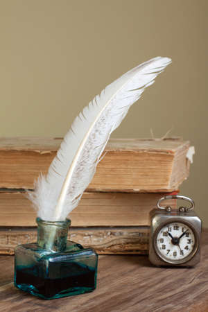 Quill and inkwell, old books, vintage clock on grunge wooden table
