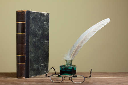 Vintage quill and inkwell, book, eyeglasses on wood photo