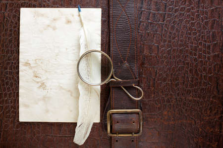 Vintage crocodile leather textured background with magnifying glass, quill and paper blank photo