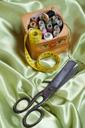 Old tailoring scissors  and threads on fabric photo