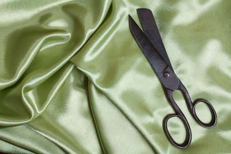 Old tailoring scissors on fabric photo
