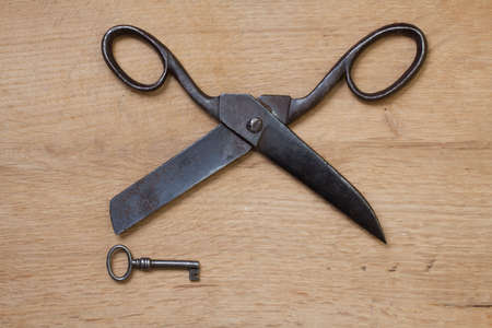 Old scissors and key on wood photo