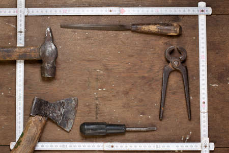Old hammer, ax, rasp, pincers on textured grunge wood in frame composition photo