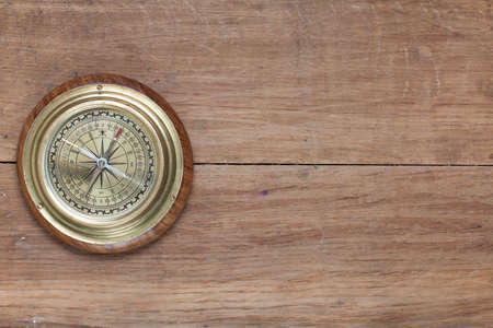 Bronze compass on the old wooden background photo