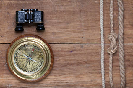 Bronze compass, binoculars and rope on wooden background photo