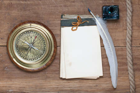 Compass, antique notebook, quill and inkwell, rope on wooden background photo