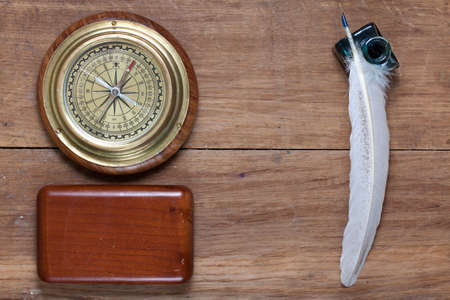 Bronze compass, quill and inkwell on old wood Stock Photo - 14666402