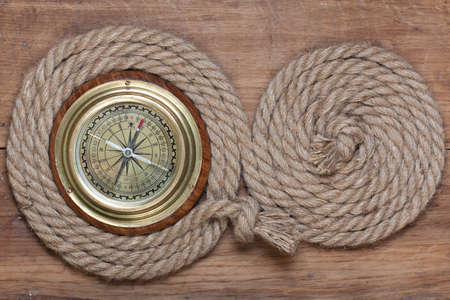 Bronze compass in rope shape on wooden background photo