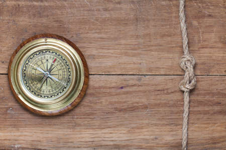 Bronze compass and rope knot on wood photo