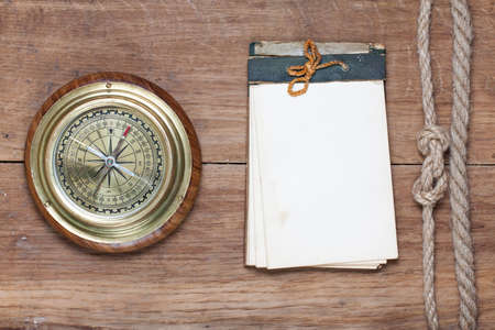 Old notebook, bronze compass, rope knot on wooden background photo