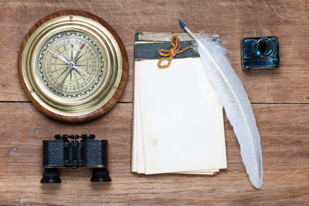 Compass, binoculars, antique notebook, quill and inkwell on wood photo