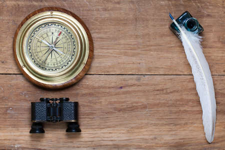 Bronze compass, binoculars, quill and inkwell on old wood photo