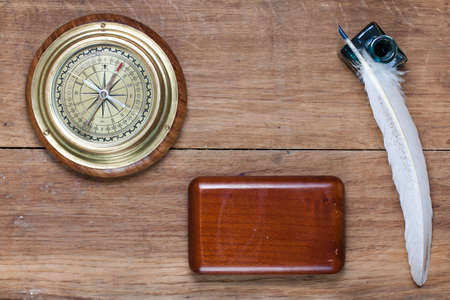 Compass, quill and inkwell on old wood photo