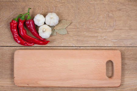 red chilly: Red chili peppers, garlic, bay leaf and kitchen board on oak wood texture background