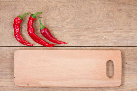 Red chili peppers and kitchen plank on oak wood texture background photo