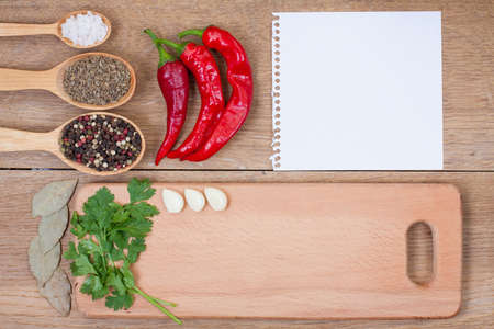 red chilly: Red chili peppers, garlic, bay leaf, spices in spoon, notebook paper and kitchen board on oak wood texture background
