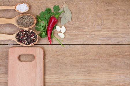 Spices in spoons, red chili pepper and kitchen board on oak wood texture background