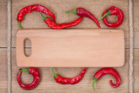Red chili peppers, kitchen plank and rope on oak wood texture background photo