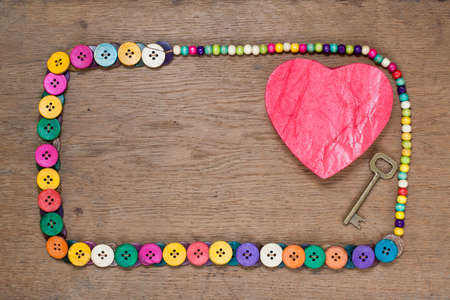 Heart shape and key in color buttons frame on wooden background photo