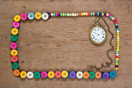Color buttons frame and vintage pocket watch on wooden background photo