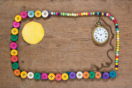 Color buttons frame, old paper tag blank and vintage pocket watch on wooden background photo