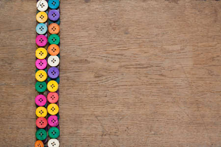 Colorful buttons on old wooden textured background photo