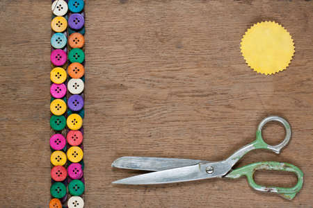 Colorful buttons, old scissors, paper label on wooden textured background photo