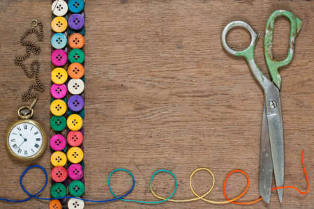 Colorful buttons, old scissors, pocket watch, color thread on oak wooden background photo