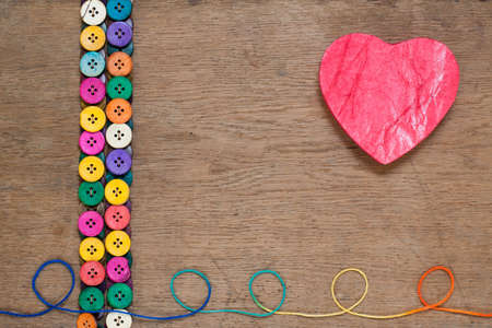 Heart shape and colorful buttons on wooden background photo