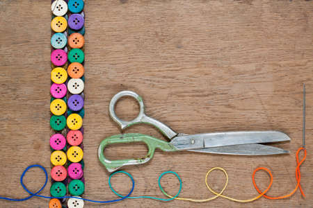Colorful buttons, old scissors, color thread on wooden textured background photo