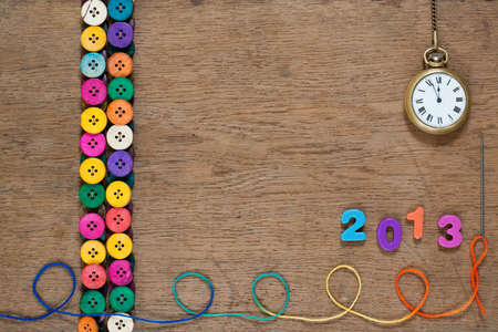 New Year, Pocket watch, colorful buttons, thread on oak wooden textured background photo