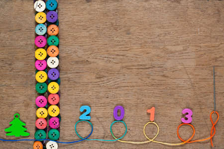 New Year number, colorful buttons, thread on oak wooden textured background photo