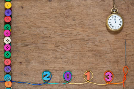 New Year number, pocket watch, colorful buttons, thread on oak wooden textured background photo