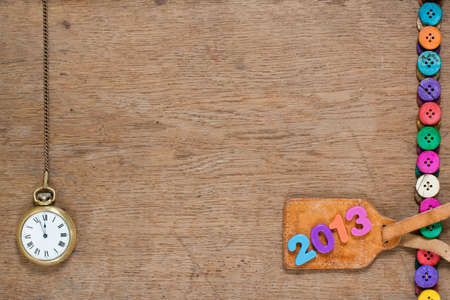 New Year number, pocket watch, colorful buttons, on oak wooden textured background photo