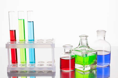 Laboratory glass test tubes with color liquid on white background photo