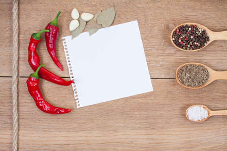 Red chilli peppers, garlic, bay leaf, spices in spoons, notebook paper on oak wood texture background photo