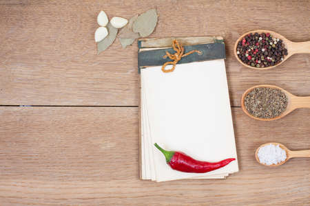 Old notebook, red chilli pepper, garlic, bay leaf, spices in spoons on oak wood texture background photo
