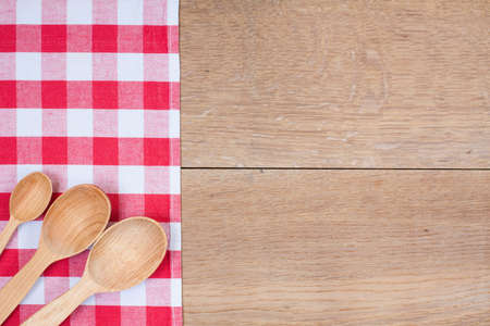 Red and white kitchen textile texture, wooden spoons on wood textured background photo
