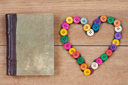 Antique book and heart shape of color buttons on wooden background photo